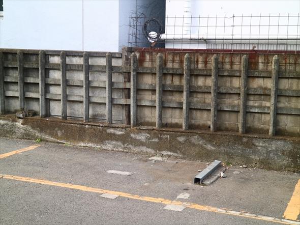 コインパーキング奥の壁。壁の手前に年季を感じさせる柵が見られます。